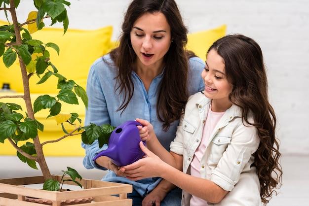 Madre e hija regando la planta