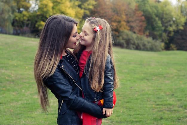 Madre e hija retrato de otoño al aire libre, familia feliz.