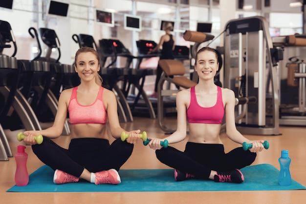 Madre e hija en ropa deportiva haciendo posturas de yoga en el gimnasio.