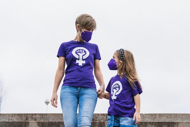 Madre e hija rubias caminando por la calle con una camiseta morada con el símbolo de las mujeres trabajadoras en el día internacional de la mujer, el 8 de marzo, y con una máscara por la pandemia de coronavirus.