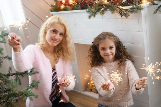 Madre e hija en la sala de estar decorada de navidad.