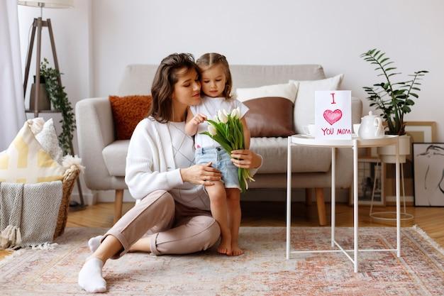 Madre e hija en el salón con un ramo de tulipanes y felicitaciones por el día internacional de la mujer