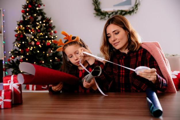 Madre e hija satisfechas envuelven regalos en papeles de colores juntos sentados a la mesa disfrutando de la época navideña en casa