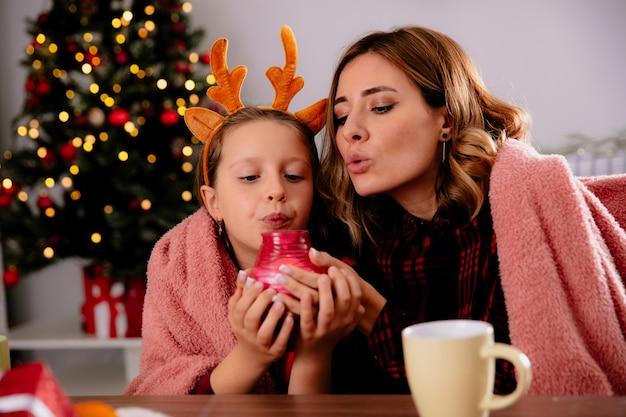 Madre e hija satisfechas con manta sosteniendo y soplando velas sentado en la mesa disfrutando de la época navideña en casa