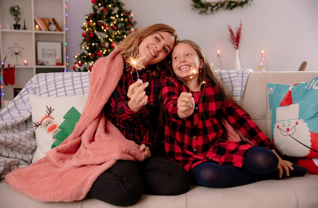 Madre e hija satisfechas sostienen bengalas cubiertas con una manta sentada en el sofá y disfrutando de la navidad en casa