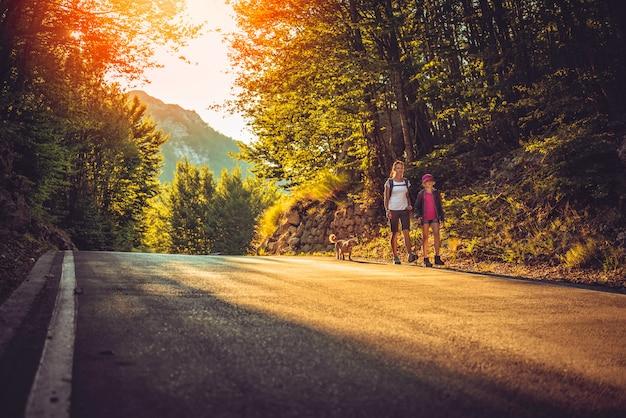 Madre e hija senderismo por la carretera de asfalto