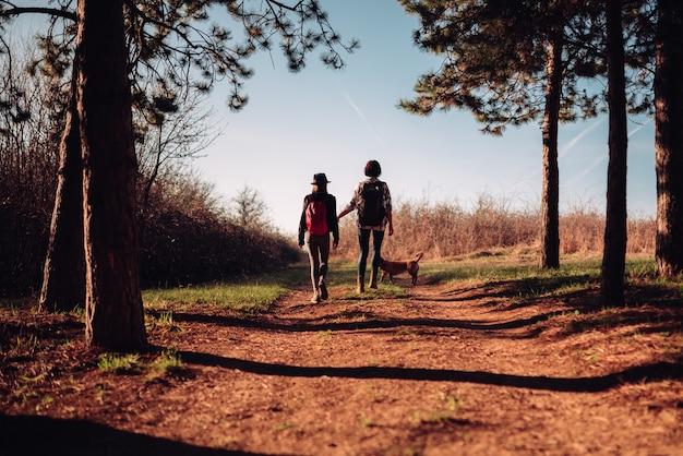 Madre e hija senderismo con perro en el sendero del bosque de pinos