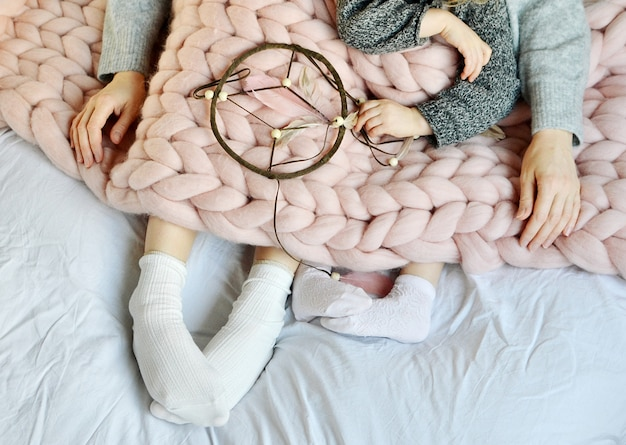 Madre e hija sentada en la cama con manta de tela escocesa de lana merina gigante rosa mañana atrapasueños familiar