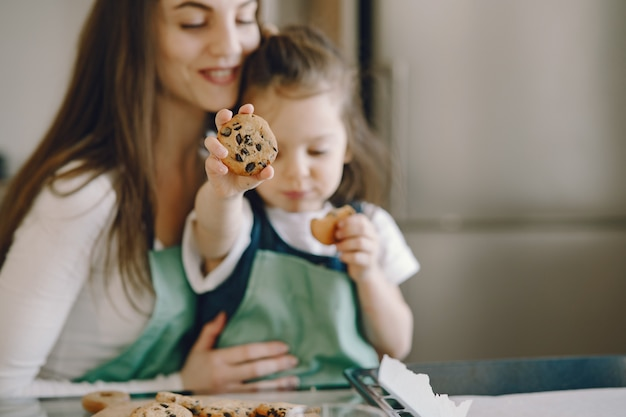 Madre e hija sentada en una cocina con galletas