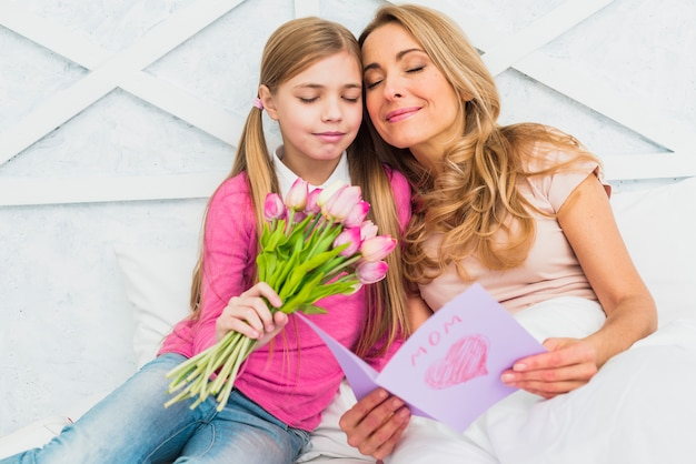 Madre e hija sentada con flores y tarjeta de felicitación