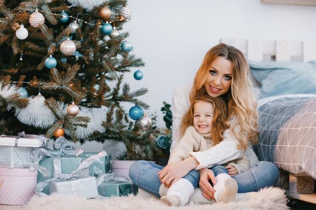 Madre e hija sentada junto al árbol de navidad
