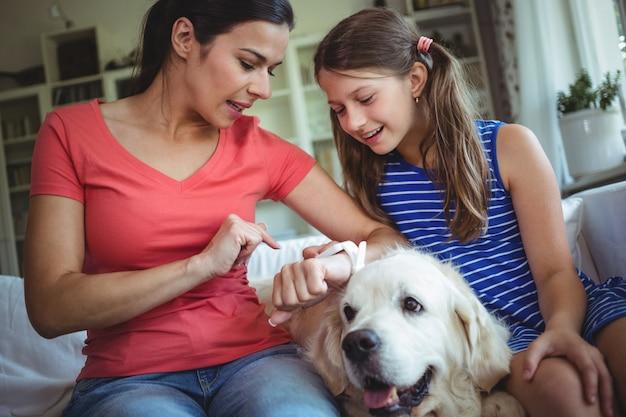 Madre e hija sentada con un perro mascota y mirando el reloj inteligente