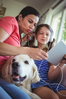 Madre e hija sentada con un perro mascota y usando digital