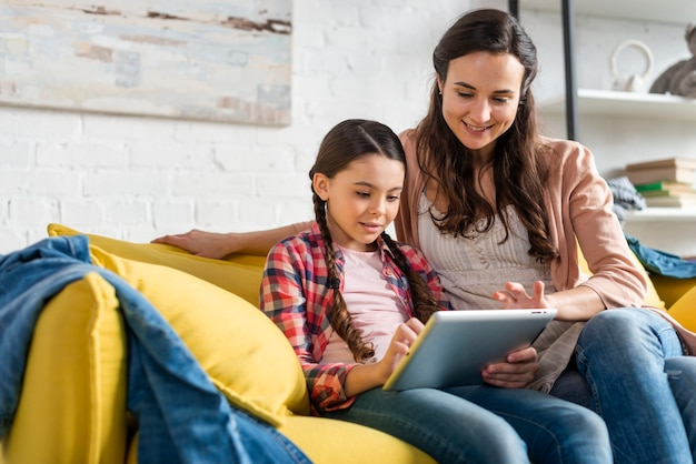 Madre e hija sentada en el sofá amarillo y leyendo