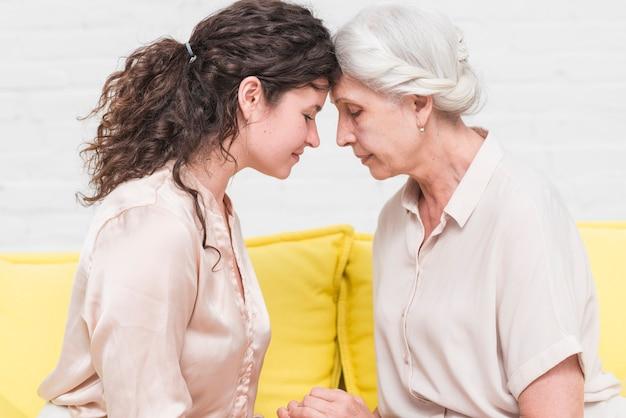 Madre e hija sentada en el sofá tocando cabezas juntos