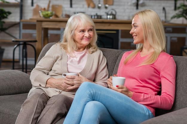 Madre e hija sentada en un sofá y tomar café