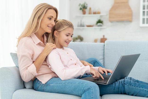 Madre e hija sentada en el sofá y trabajando en la computadora portátil