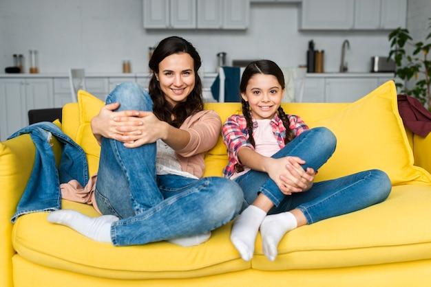 Madre e hija sentada en el sofá