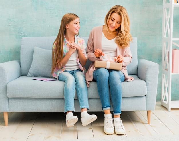 Madre e hija sentadas juntas y abriendo caja actual