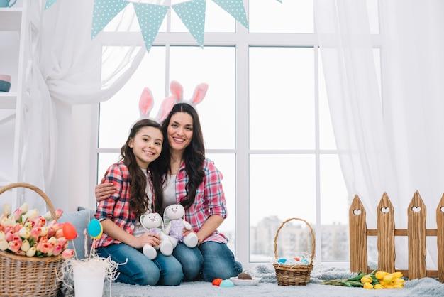 Madre e hija sentadas juntas sosteniendo un conejito de peluche en la celebración de pascua