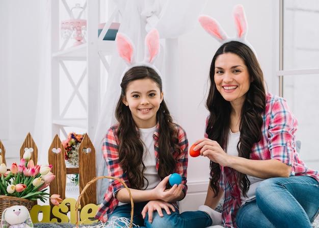 Madre e hija sentadas juntas sosteniendo huevos de pascua rojos y azules en la mano