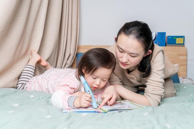 Madre e hija se sientan en la cama leyendo juntas