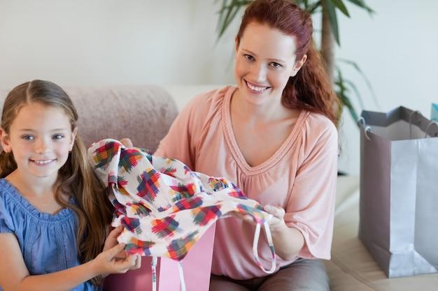 Madre e hija en el sofá con compras