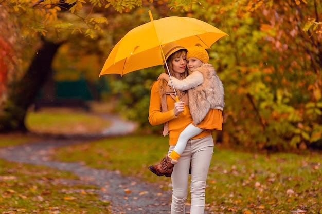 Madre e hija bajo una sombrilla amarilla para pasear por el parque