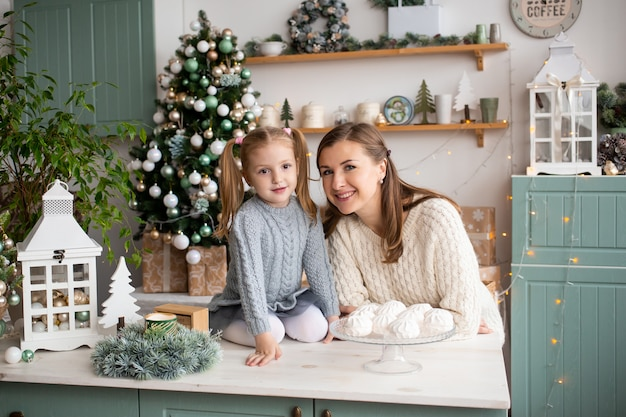 Madre e hija sonriendo en la cocina de navidad en casa.
