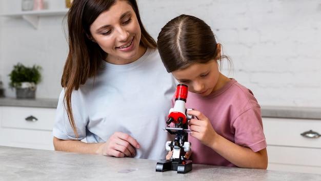 Madre e hija sonrientes haciendo experimentos con microscopio