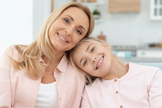 Madre e hija sonrientes mirando al fotógrafo
