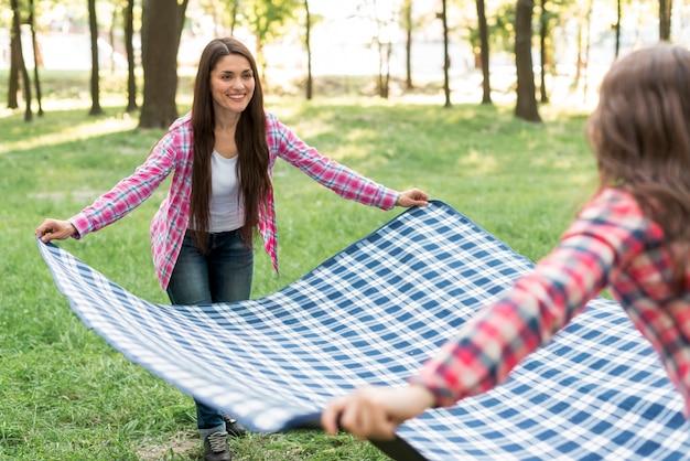 Madre e hija sonrientes que colocan la manta a cuadros azul en hierba verde