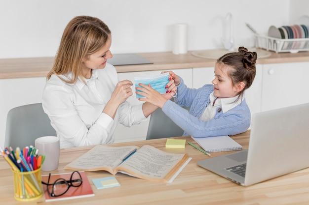 Madre e hija sosteniendo una máscara médica