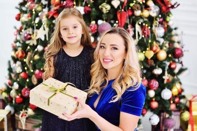 Madre e hija sosteniendo un regalo de navidad sonriendo en el fondo del árbol de navidad.