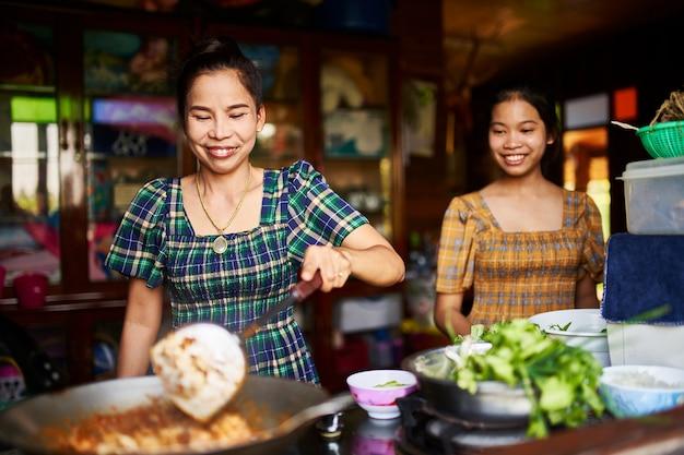 Madre e hija tailandesas cocinar juntos en cocina rústica haciendo curry rojo