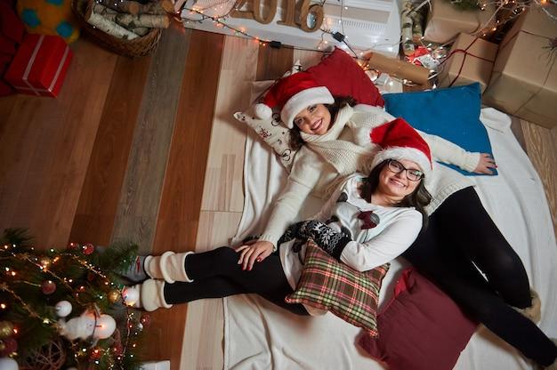 Madre e hija tendidas en el suelo juntas en casa en navidad