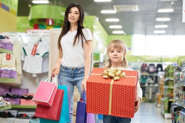 Madre e hija en la tienda con bolsas de compras y caja de regalo