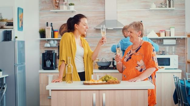 Madre e hija tintinean vasos de vino sentados en la cocina. familia extendida celebrando en el comedor bebiendo una copa de vino mientras los hombres están cocinando en el fondo
