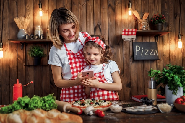 Madre e hija toman fotos de pizza cocinada en un teléfono inteligente