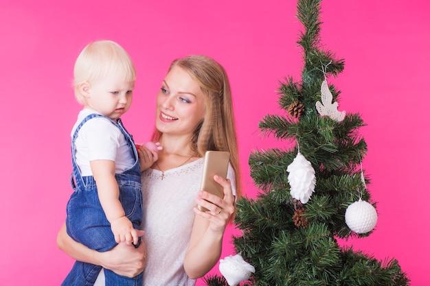 Madre e hija tomando un selfie cerca del árbol de navidad