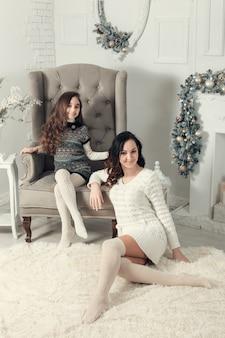 Madre e hija ubicadas en un sofá en navidad decorado habitación