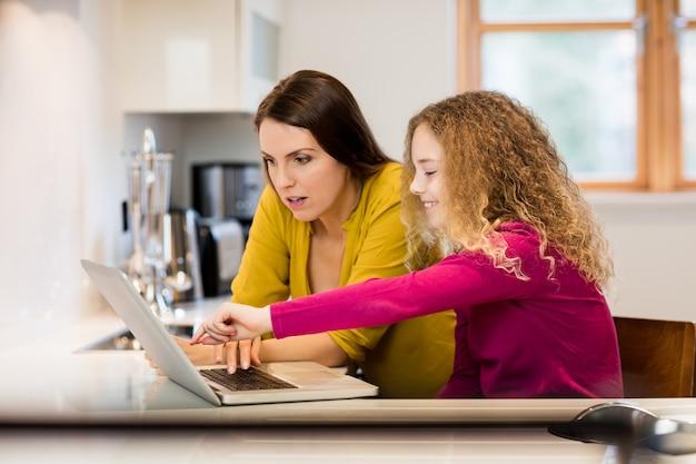 Madre e hija usando la computadora portátil en la cocina