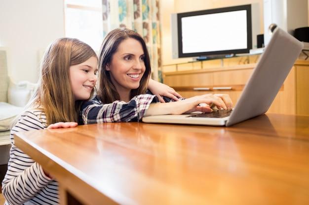 Madre e hija usando la computadora portátil en la sala de estar