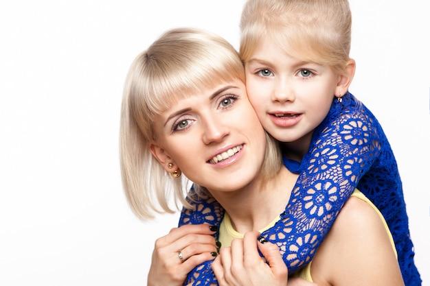 Madre e hija en vestido colorido sobre fondo blanco.