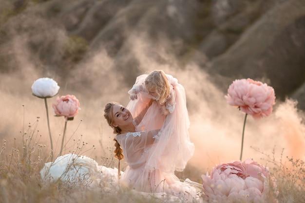 Madre e hija con vestidos de cuento de hadas rosados juegan en un campo rodeado de grandes flores decorativas de color rosa