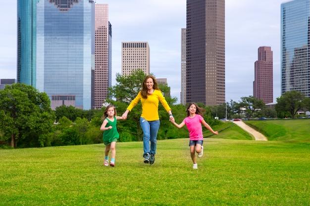 Madre e hijas caminando tomados de la mano en el horizonte de la ciudad