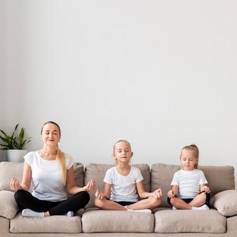 Madre e hijas meditando en el sofá en casa