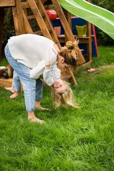 Madre e hijas pasan el tiempo en un columpio y un tobogán para niños. mamá con hijos tiempo juntos.