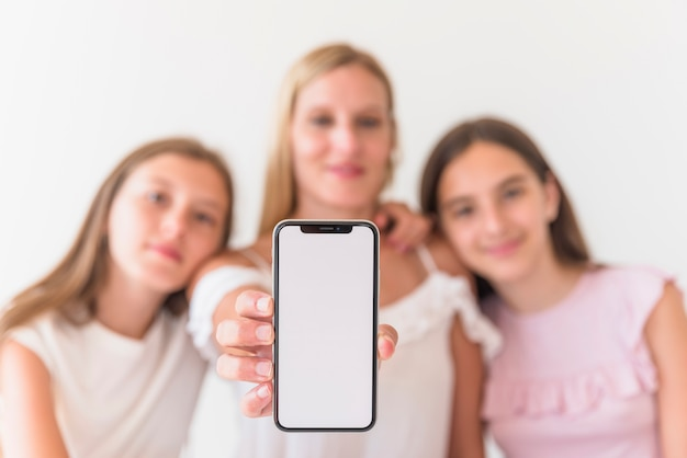 Madre e hijas sosteniendo teléfono inteligente con pantalla en blanco