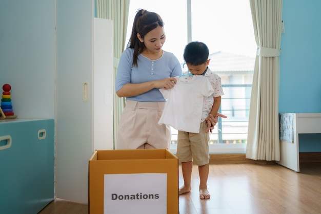 Madre e hijo asiáticos están parados cerca de un armario de ropa en el vestidor llevando una caja de ropa donada para llevar al centro de donación.